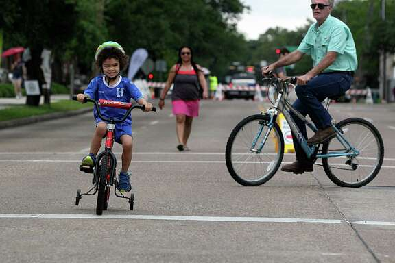 Four-year-old Chauncy Rowe-Watters left, rides his bike during the 2016 Spring Season of Cigna Sunday Streets event in Museum Park Sunday, April 24, 2016, in Houston.
