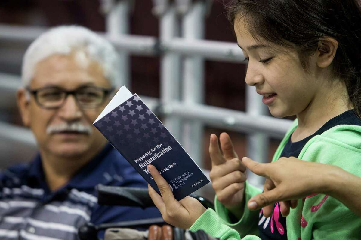 Mia Macias quizzes her uncle Fidel Lemus from the naturalization test pamphlet as they attend a recent citizenship workshop at the M.O. Campbell Center in Houston.