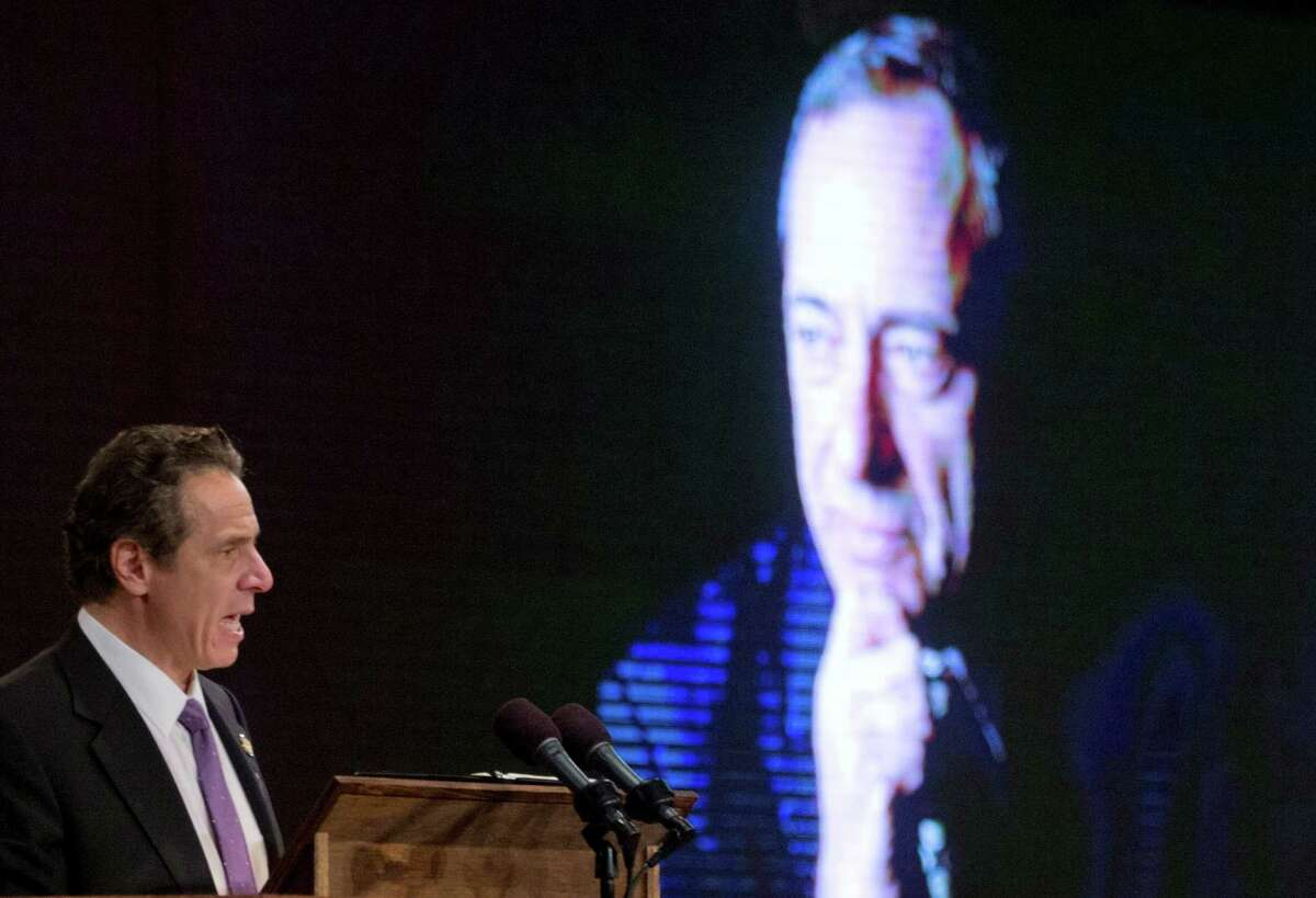 With a portrait of his father and former New York Gov. Mario Cuomo on a screen, Gov. Andrew Cuomo delivers his State of the State address and executive budget proposal at the Empire State Plaza Convention Center on Wednesday, Jan. 13, 2016, in Albany, N.Y. (AP Photo/Mike Groll)