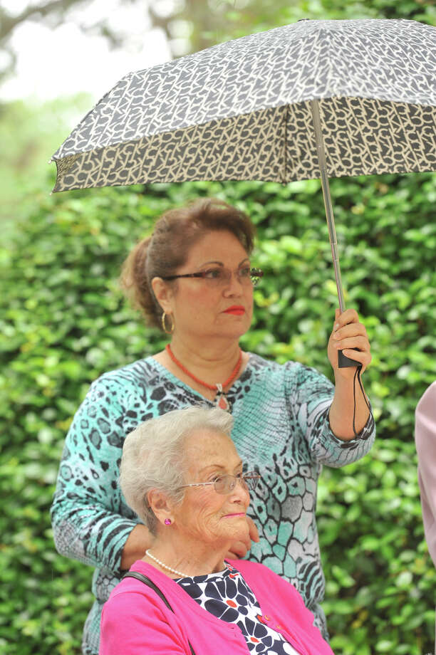 Judith Miramontes,  holds an umbrella over her mother,  Maria Luisa Miramontes as a light rain began to fall on the Celebracion del Dia de las Madres mass at the Our Lady of Lourdes Grotto Sunday. Photo: Robin Jerstad, San Antonio Express-News