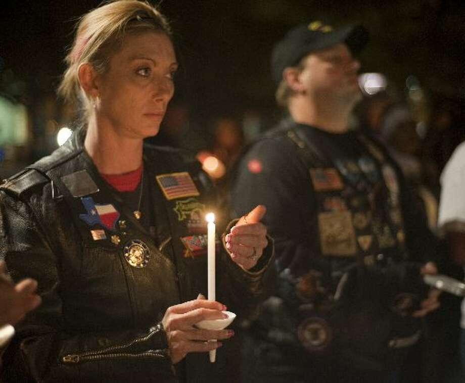 Members of the Patriot Guard Riders and community light candles Friday night at a memorial vigil for the Show of Support train accident victims last year.