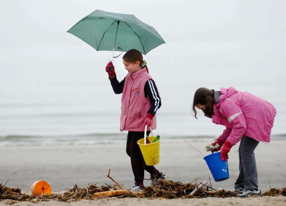 Girl Scouts from Troop 50650 of Old Greenwich, Olivia Dallape, 10, left, and Talia Newman, also 10, clear the beach at Greenwich Point of garbage during the Greenwich Green & Clean's annual townwide cleanup, Saturday morning, April 17, 2010. Photo: Bob Luckey / Greenwich Time