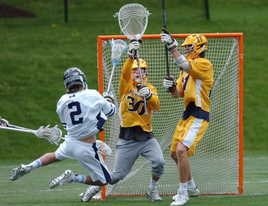 Jack Rogan, Brunswick goalie, stops a point-blank shot by Pierson Fowler, # 2, during lst quarter action of game against Hotchkiss, at Brunswick, Saturday, April 17, 2010.  At right is Brunswick's Philip Pierce. Photo: Bob Luckey / Greenwich Time