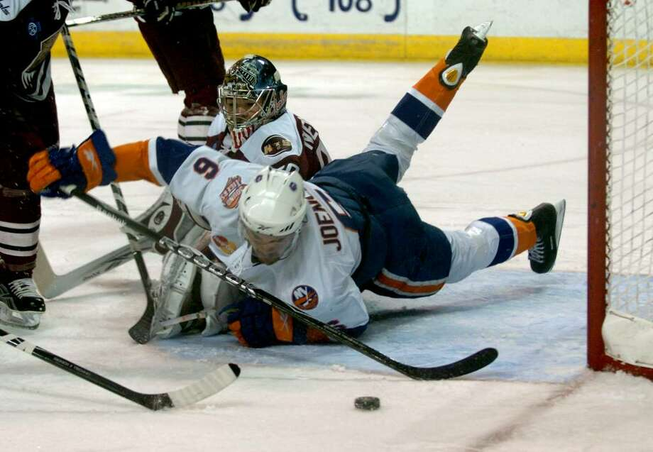 Sound Tigers' #6 Jesse Joensuu trips over Hershey's goalie Michal Neuvirth as he tries to get to the puck, during playoff action at the Arena at Harbor Yard in Bridgeport, Conn. on Saturday April 17, 2010. Sound Tigers fell to Hershey 7-2. Photo: Christian Abraham / Connecticut Post