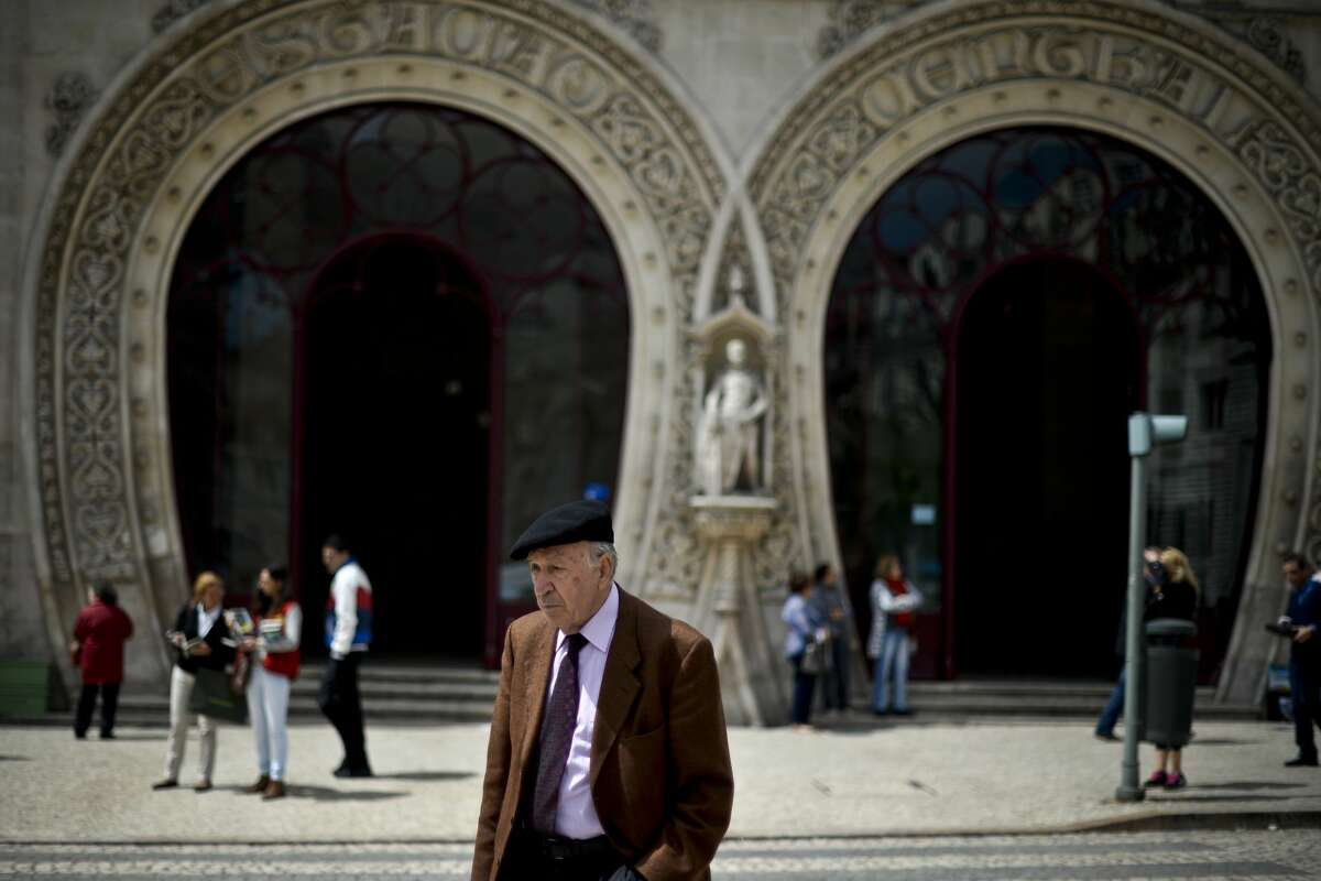 A man passes in front of Rossio Train Station in central Lisbon. The statue of Dom Sebastiao is visible in the background.