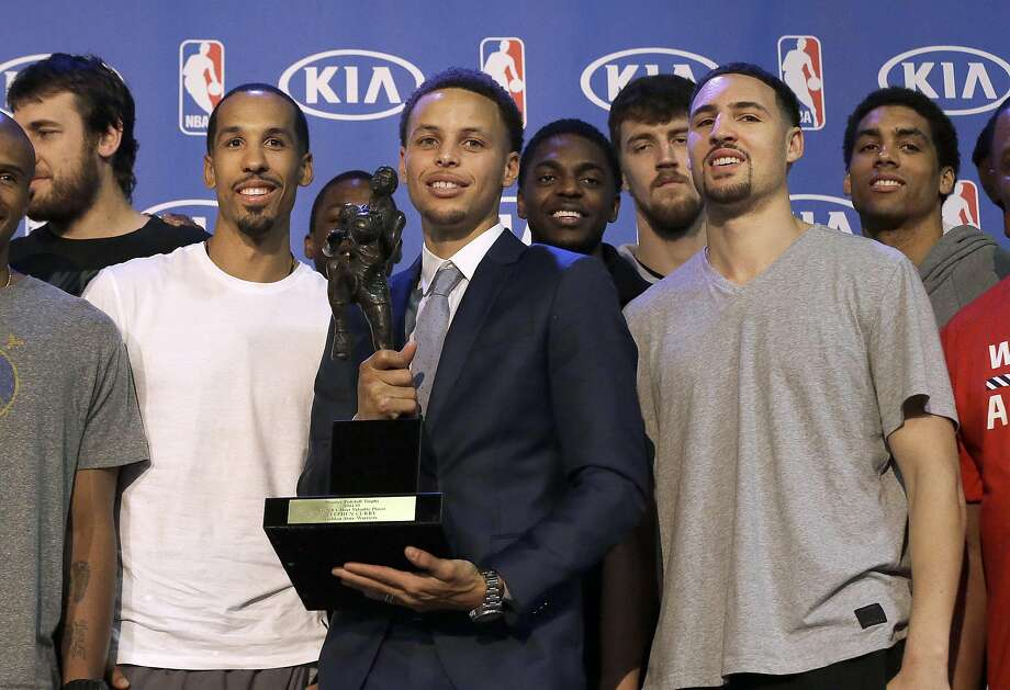 Golden State Warriors guard Stephen Curry, center, poses for photos with teammates and coaches at a basketball news conference announcing him as the NBA's Most Valuable Player Monday, May 4, 2015, in Oakland, Calif. Curry carried the top-seeded Warriors to a franchise-record 67 wins and surpassed his own record for most 3-pointers in a season. (AP Photo/Jeff Chiu) Photo: Jeff Chiu, Associated Press