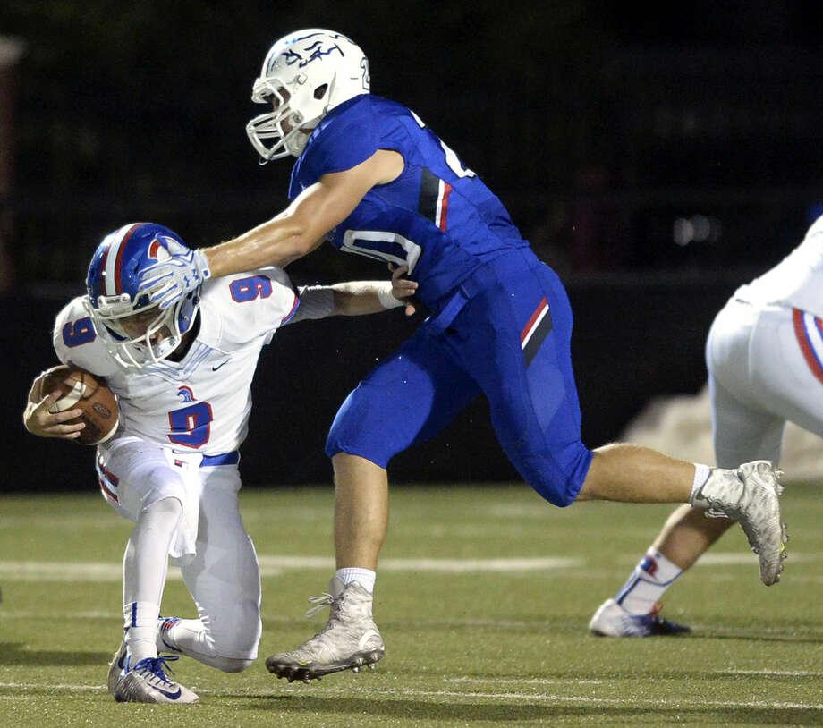 Midland Christian middle linebacker Garrett Eddison (20) roughs up Addison Trinity quarterback Sam Clare (9) on Friday, Oct. 2, 2015, at Mustang Field. James Durbin/Reporter-Telegram