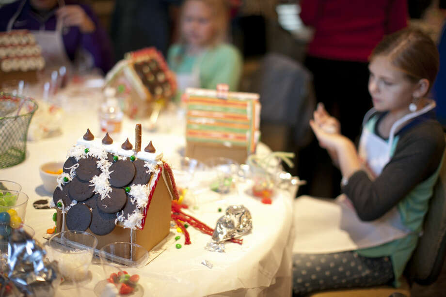 Children gather candies to decorate their gingerbread house at last year's Gingerbread Haven. Photo: James Durbin