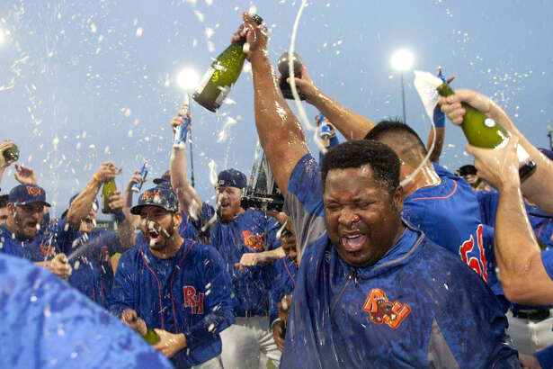 Rockhounds hitting coach Webster Garrison hoists a champaign bottle while team members celebrate a 5-0 win over Tulsa in the final game of the Texas League Championship series Sunday at Security Bank Ballpark. James Durbin/Reporter-Telegram