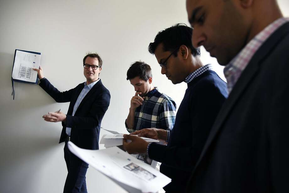 Gert Christen (left), of City Innovate, goes plans with Andrew McMahon, Jay Nath and Kamran Saddigue during a tour of the future home of the Superpublic innovation lab at 50 United Nations Plaza in San Francisco. Photo: Michael Short, Special To The Chronicle