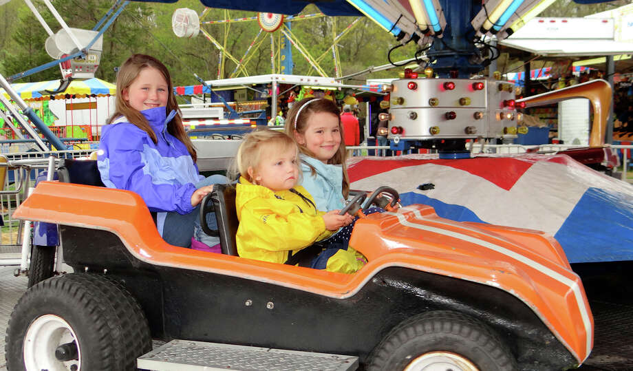 Sisters Teaghan, Evaly and Calyn Fletcher, ages 7, 2 and 5, of Fairfield, take a turn on the Umbrella Ride at Riverfield Elementary School's carnival on Saturday. Photo: Fairfield Citizen / Mike Lauterborn / Fairfield Citizen