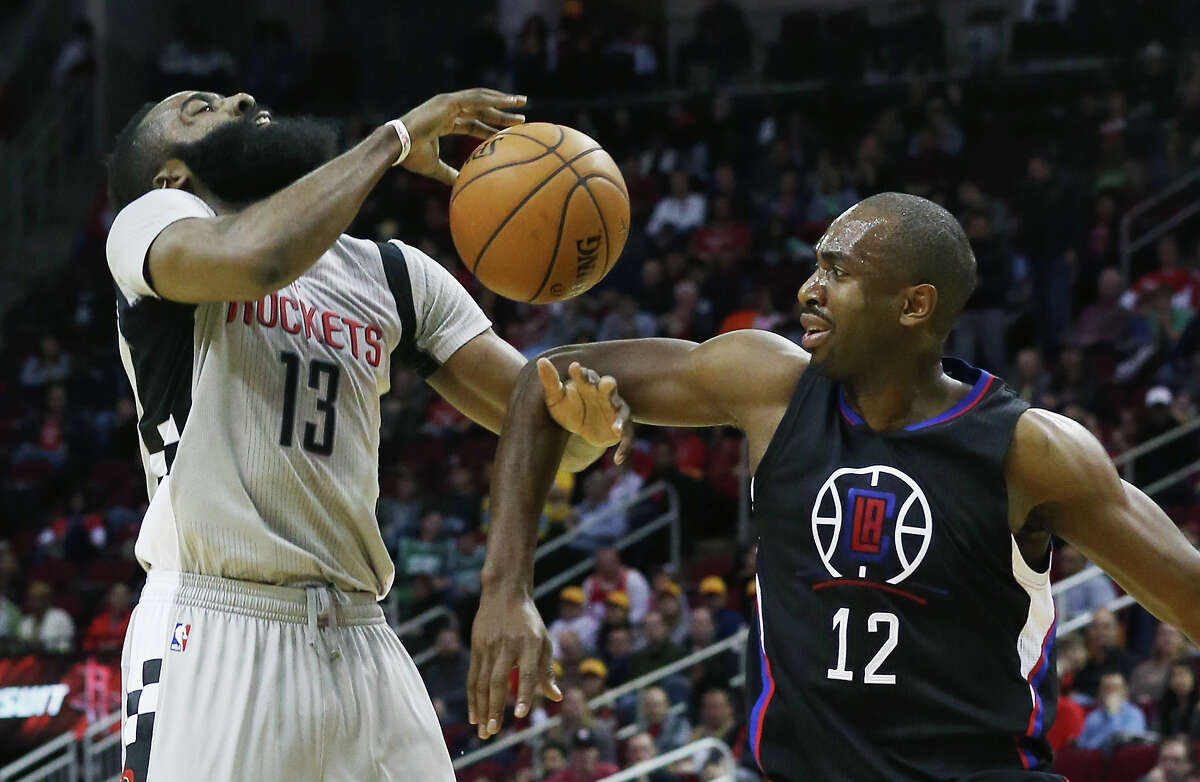 HOUSTON, TX - DECEMBER 19: James Harden #13 of the Houston Rockets and Luc Mbah a Moute #12 of the Los Angeles Clippers battle for the basketball during their game at Toyota Center on December 19, 2015 in Houston, Texas. NOTE TO USER: User expressly acknowledges and agrees that, by downloading and or using this Photograph, user is consenting to the terms and conditions of the Getty Images License Agreement. (Photo by Scott Halleran/Getty Images)