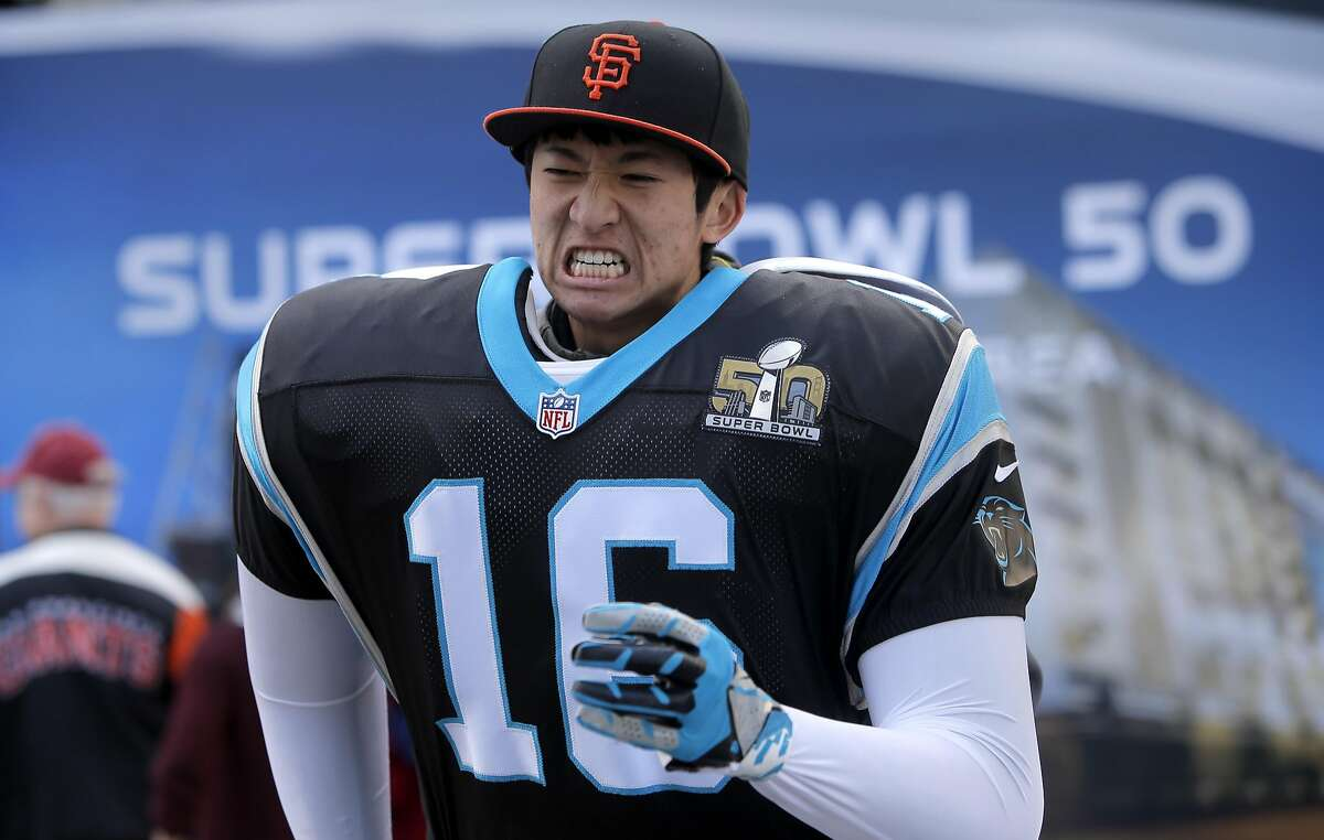Harrison Jow, 18 shows his grit for a photo as a Carolina Panther during the opening day of the free fan experience Super Bowl City at the foot of Market St. in downtown San Francisco, Calif., on Sat. January 30, 2016