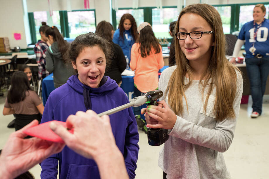 Alessia and Timea, sixth graders at Scofield Magnet Middle School in Stamford, participate in a demostration of medical tools from Medtronic, a medical technology company. Photo: Kyle Michael King / For Hearst Connecticut Media / Stamford Advocate freelance