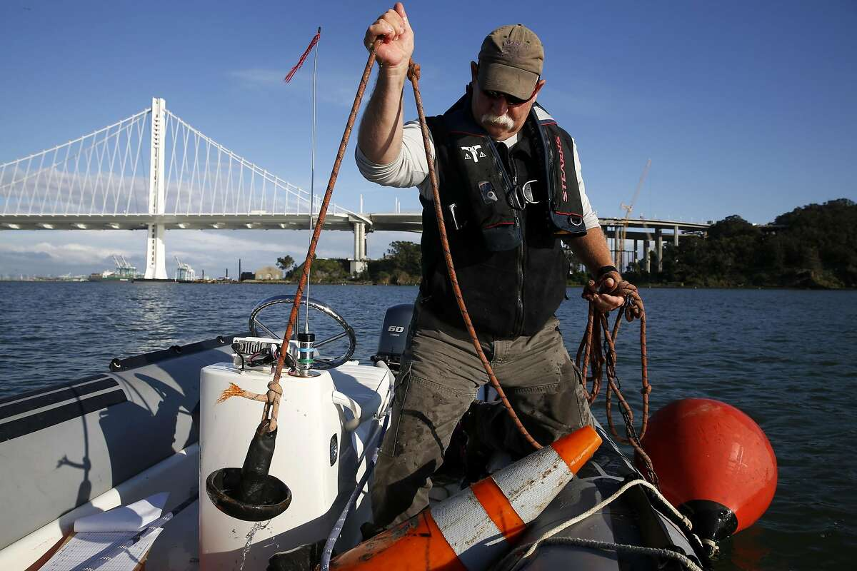 Ian McClelland lifts the anchor of a sailboat racing mark to throw in the water of Clipper Cove off Treasure Island, California, on Thursday, May 5, 2016.