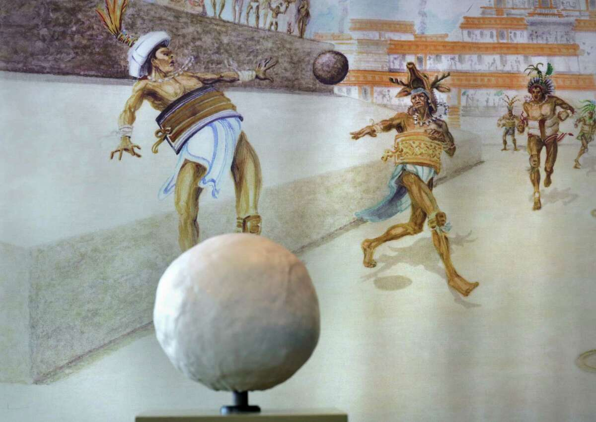 A painting depicting the sacred Mayan ball game is seen behind a seven pound rubber ball like the ones used in the cermonial game that sometimes culminated in human sacrifice. The Witte Museum is about ready to open the exhibit
