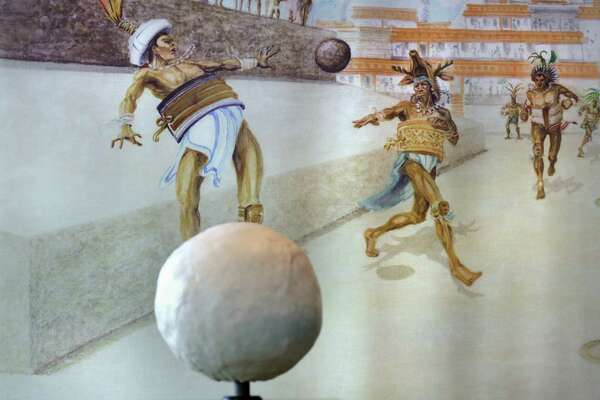 """A painting depicting the sacred Mayan ball game is seen behind a seven pound rubber ball like the ones used in the cermonial game that sometimes culminated in human sacrifice. The Witte Museum is about ready to open the exhibit """"Maya:Hidden Worlds Revealed"""" in the Mays Family Center. Museum workers were putting final touches on the exhibit on Monday, May 9, 2016."""
