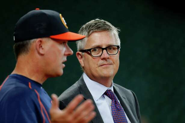 Houston Astros GM Jeff Luhnow talks with manager A.J. Hinch during batting practice before the start of an MLB baseball game at Minute Maid Park, Monday, May 9, 2016, in Houston.