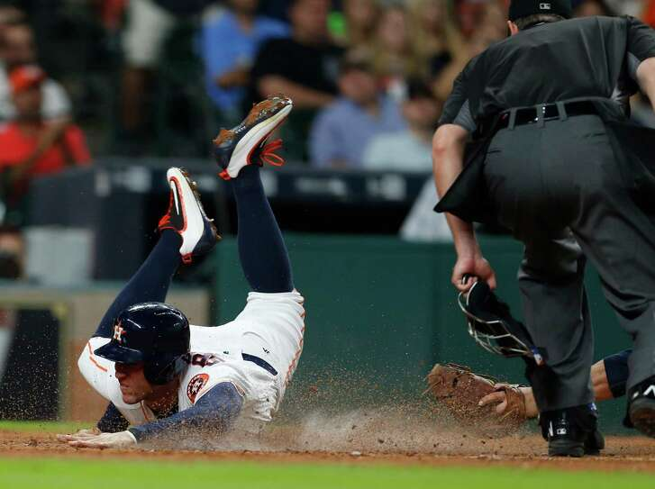 Houston Astros right fielder George Springer (4) dives into home to score a run on Colby Rasmus' two-run single during the third inning of an MLB baseball game at Minute Maid Park, Monday, May 9, 2016, in Houston.