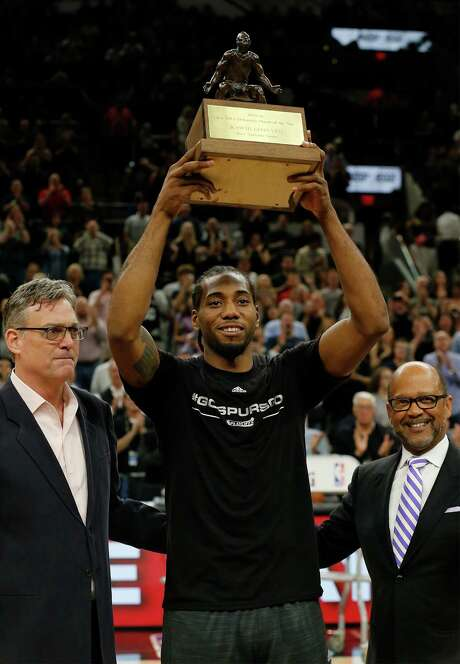 Spurs' Kawhi Leonard (center) holds up the KIA Defensive Player of the Year trophy alongside Spurs' General Manager R.C. Buford (left) before the start of Game 2 against the Memphis Grizzlies at the AT&T Center in the first round of Western Conference playoffs on Tuesday, Apr. 19, 2016. (Kin Man Hui/San Antonio Express-News) Photo: Kin Man Hui, Staff / San Antonio Express-News / ©2016 San Antonio Express-News
