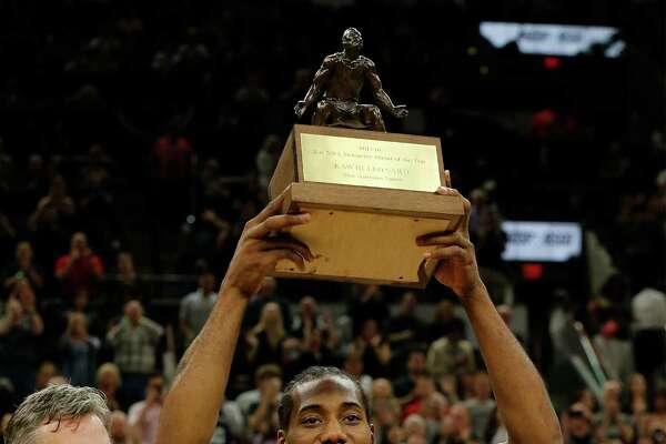 Spurs' Kawhi Leonard (center) holds up the KIA Defensive Player of the Year trophy alongside Spurs' General Manager R.C. Buford (left) before the start of Game 2 against the Memphis Grizzlies at the AT&T Center in the first round of Western Conference playoffs on Tuesday, Apr. 19, 2016. (Kin Man Hui/San Antonio Express-News)