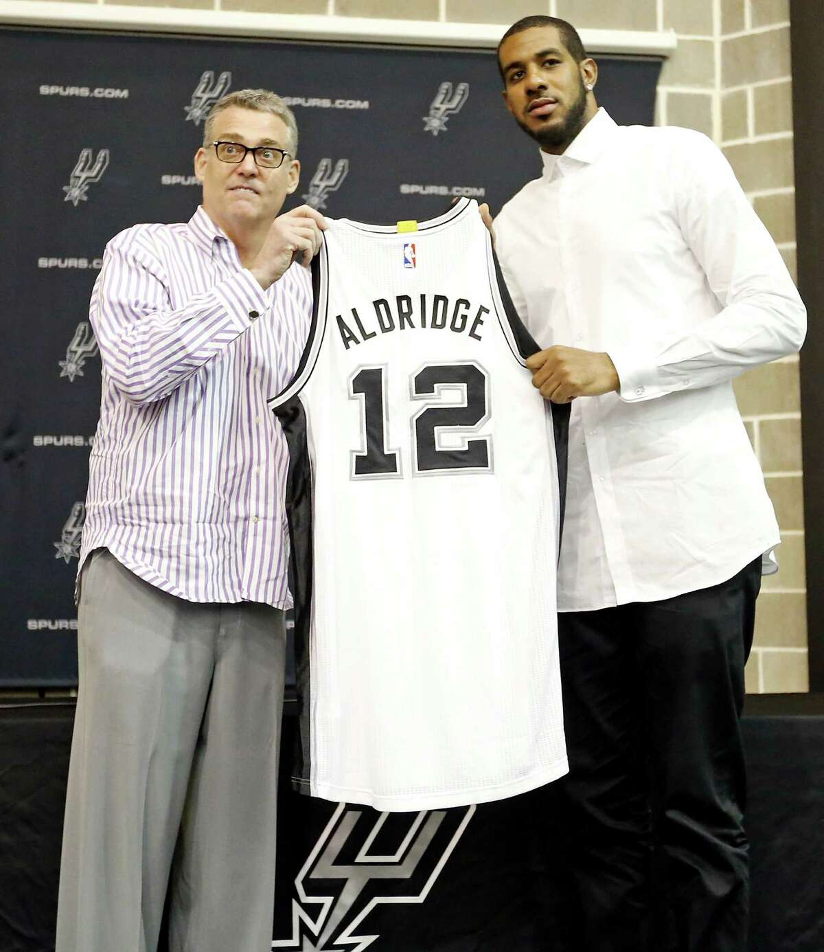 San Antonio Spurs general manager R.C. Buford (left), and LaMarcus Aldridge pose for photos with Aldridge's jersey during a press conference at the Spurs practice facility Friday July 10, 2015 where he was officially introduced.