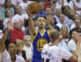 Golden State Warriors guard Stephen Curry, center, shoots over Portland Trail Blazers guard C.J. McCollum, left, and Portland Trail Blazers center Mason Plumlee, right, during the second half of Game 4 of an NBA basketball second-round playoff series Monday, May 9, 2016, in Portland, Ore. (AP Photo/Craig Mitchelldyer)