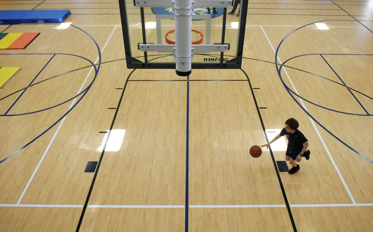 Whitby School seventh-grader Adem Murad dribbles a basketball through the new gymnasium and athletic facility at Whitby School in Greenwich, Conn. Tuesday, April 20, 2016. The new space, which was completed about a month ago, includes a basketball court, climbing wall, classroom, teachers' office and dance studio.