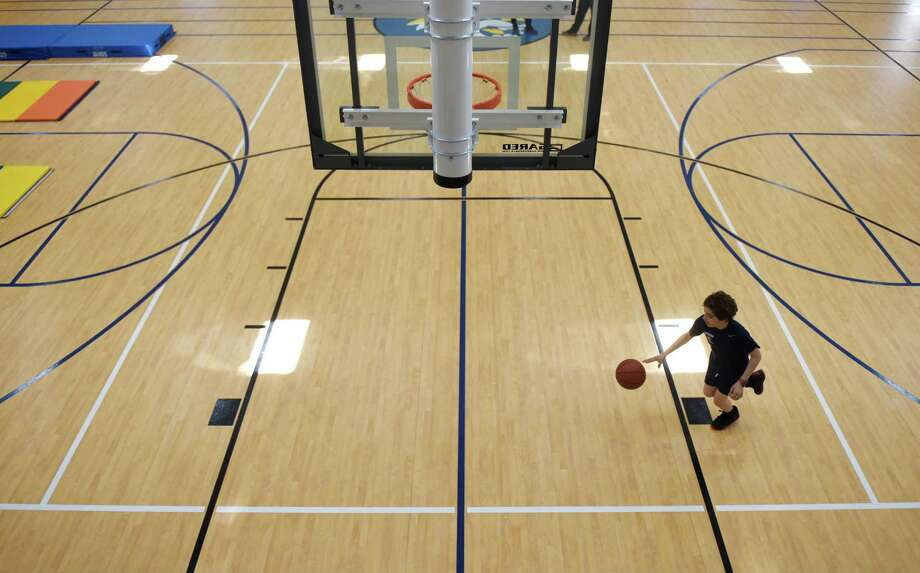 Whitby School seventh-grader Adem Murad dribbles a basketball through the new gymnasium and athletic facility at Whitby School in Greenwich, Conn. Tuesday, April 20, 2016. The new space, which was completed about a month ago, includes a basketball court, climbing wall, classroom, teachers' office and dance studio. Photo: Tyler Sizemore / Hearst Connecticut Media / Greenwich Time