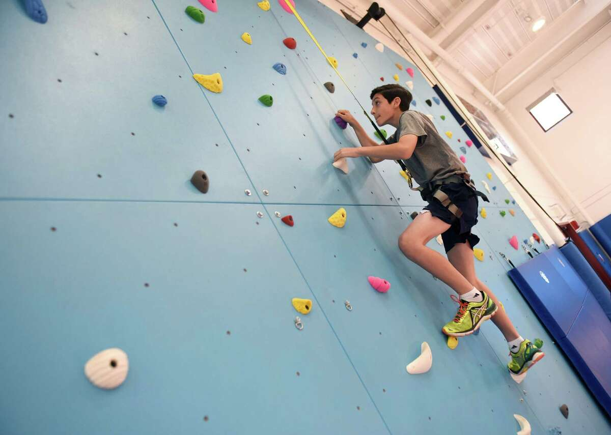 Whitby School seventh-grader Ben O'Brien climbs the rock wall inside the new gymnasium and athletic facility at Whitby School in Greenwich, Conn. Tuesday, April 20, 2016. The new space, which was completed about a month ago, includes a basketball court, climbing wall, classroom, teachers' office and dance studio.