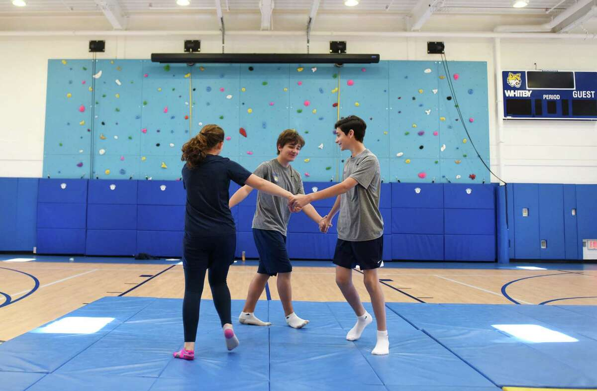 Whitby School seventh-graders Malia Monge, left, Alexy Theuerkauf, center, and Ben O'Brien practice a gymnastics routine on a mat in the new gymnasium and athletic facility at Whitby School in Greenwich. The new space, completed about a month ago, includes a basketball court, climbing wall, classroom, teachers' office and dance studio.