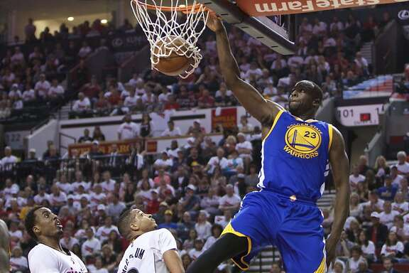 Golden State Warriors forward Draymond Green, right, dunks over Portland Trail Blazers forward Al-Farouq Aminu, left, and C.J. McCollum, center, during the first half of Game 4 of an NBA basketball second-round playoff series Monday, May 9, 2016, in Portland, Ore. (AP Photo/Craig Mitchelldyer)