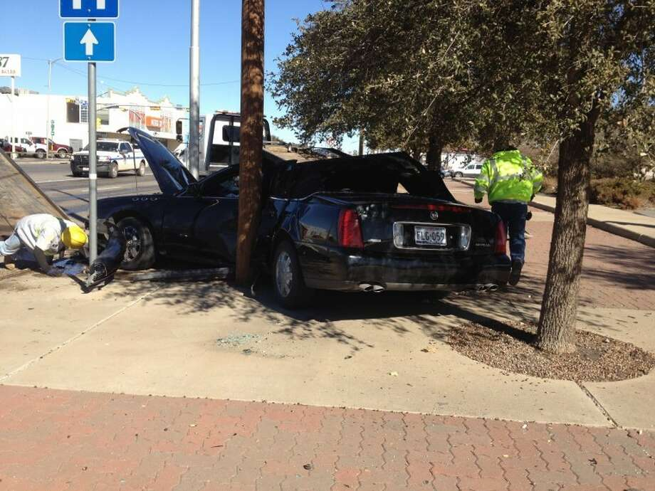 Santiago G. Bruno, 63, was driving this Cadillac DeVille around 12:30 p.m. Monday when he lost control while headed west on Wall Street, struck a pole and then wrapped his car around a second pole. Midland police said they believe Bruno had been traveling at speeds of up to 80 mph. After receiving treatment for non-life threatening injuries at Midland Memorial Hospital, Bruno was charged with retaliation, driving while intoxicated and possession. Photo: Kathleen Thurber/MRT Staff