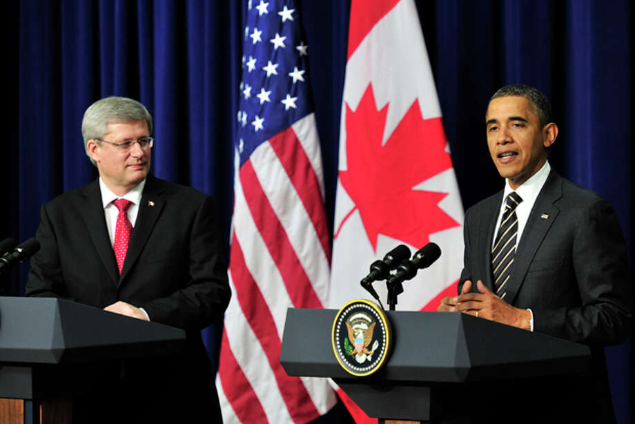Canadian Prime Minister Stephen Harper, left, listens as U.S. President Barack Obama speaks following a meeting at the White House in Washington on Wednesday, Dec. 7, 2011. President Obama warned congressional Republicans that he would reject any effort to tie extraneous issues to an extension of the payroll tax cut, including the approval of an oil pipeline between the U.S. and Canada. (AP Photo/The Canadian Press, Paul Chiasson) Photo: Paul Chiasson / The Canadian Press