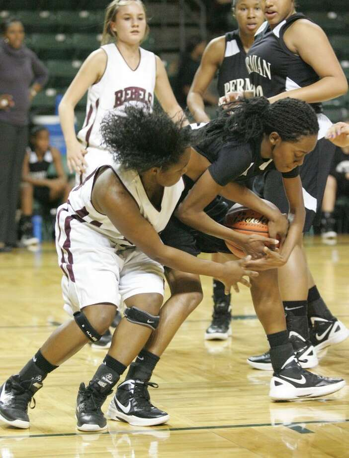 Lee's Jaylaan Lee (24) and Permian's Cheyene Swoopes (12) battle for possession of the ball Tuesday during their game at Chaparral Center. Photo: Cindeka Nealy