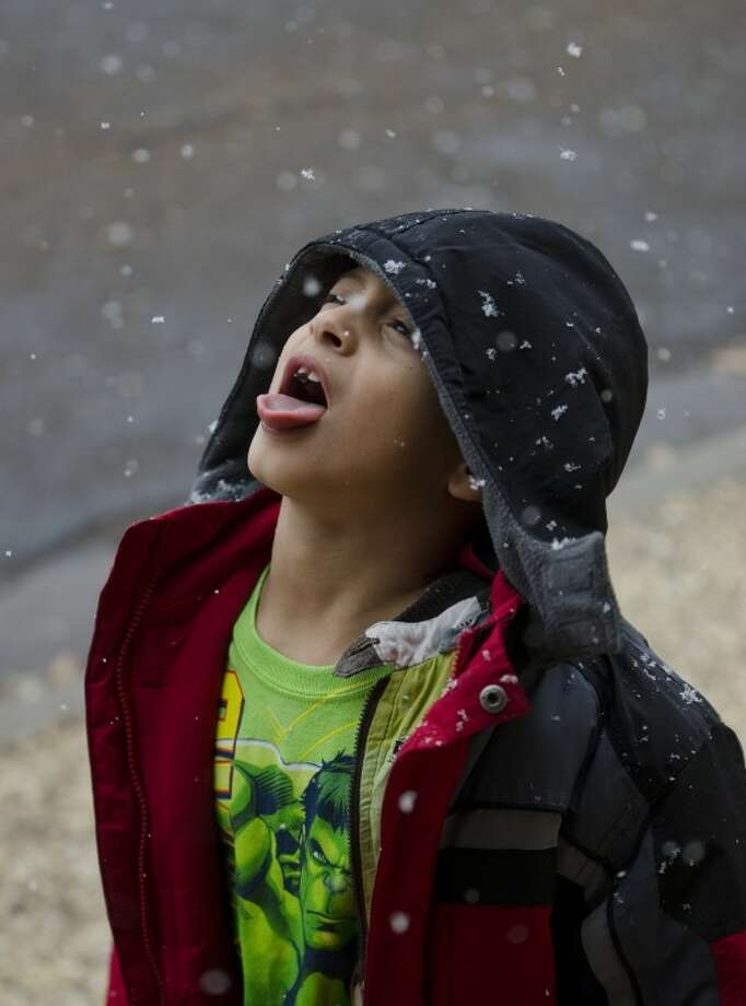 Julius Bueno, 7, catches snow flakes on his tongue Thursday afternoon. Bueno is in town for the New Years holiday from California to visit family. Tim Fischer\Reporter-Telegram Photo: Tim Fischer