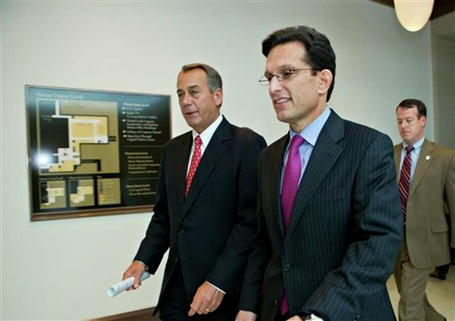 """Speaker of the House John Boehner, R-Ohio, left, joined by House Majority Leader Eric Cantor, R-Va., returns to his office after speaking to reporters on the fiscal cliff negotiations, at the Capitol in Washington, Friday, Dec. 21, 2012. Hopes for avoiding the """"fiscal cliff"""" that threatens the U.S. economy fell Friday after fighting among congressional Republicans cast doubt on whether any deal reached with President Barack Obama could win approval ahead of automatic tax increases and deep spending cuts kick in Jan. 1. (AP Photo/J. Scott Applewhite) Photo: J. Scott Applewhite / AP"""
