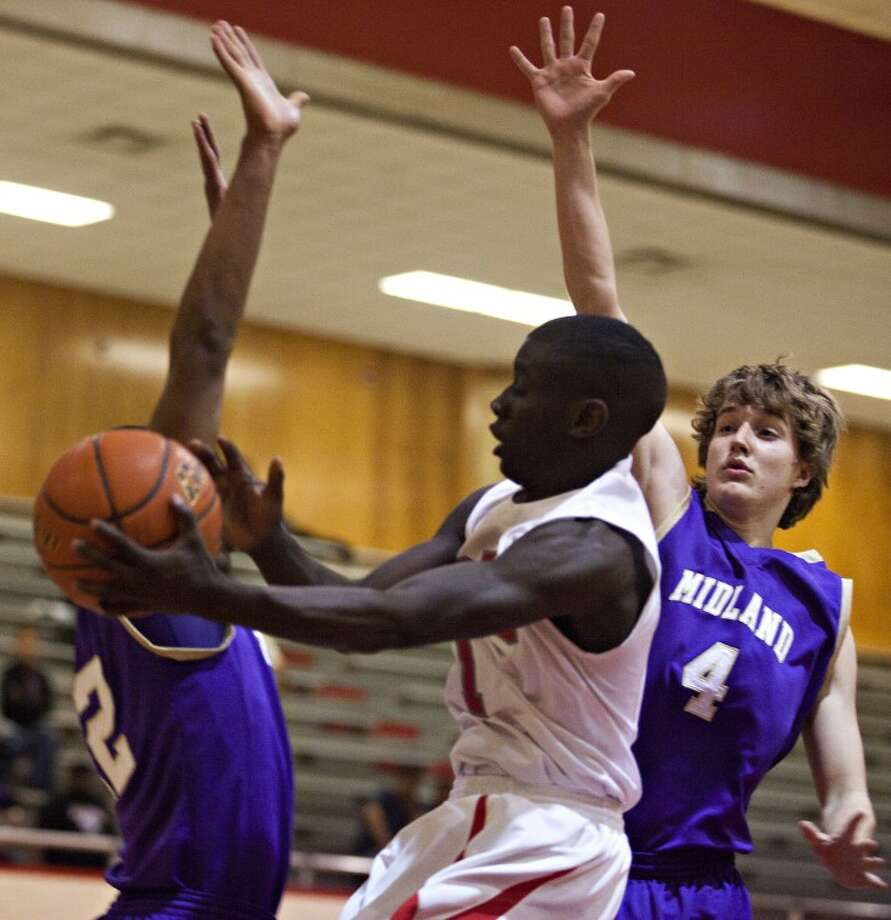 Odessa High's Isaiah Deary (1) passes the ball as Midland High's Jacob MaKowsky (4) and TJ Brown (12) guard him during the game Tuesday at the Odessa High Field House. Photo: Albert Cesare/Odessa American
