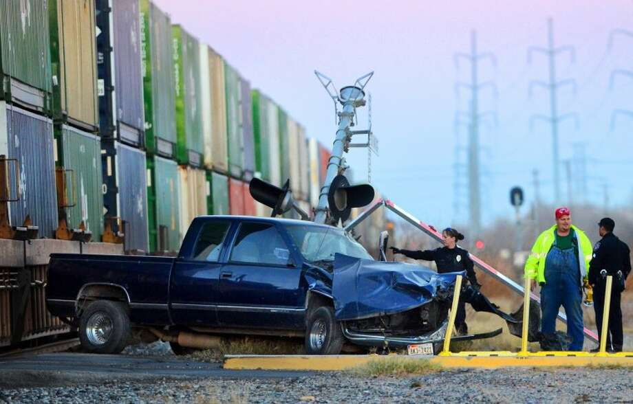 Midland emergency personne investigate the scene after a truck traveling northbound on Carver St. was struck by a train Saturday. The driver was the only occupant and was transported to Midland Memorial Hospital with minor injuries. James Durbin/Reporter-Telegram Photo: JAMES DURBIN