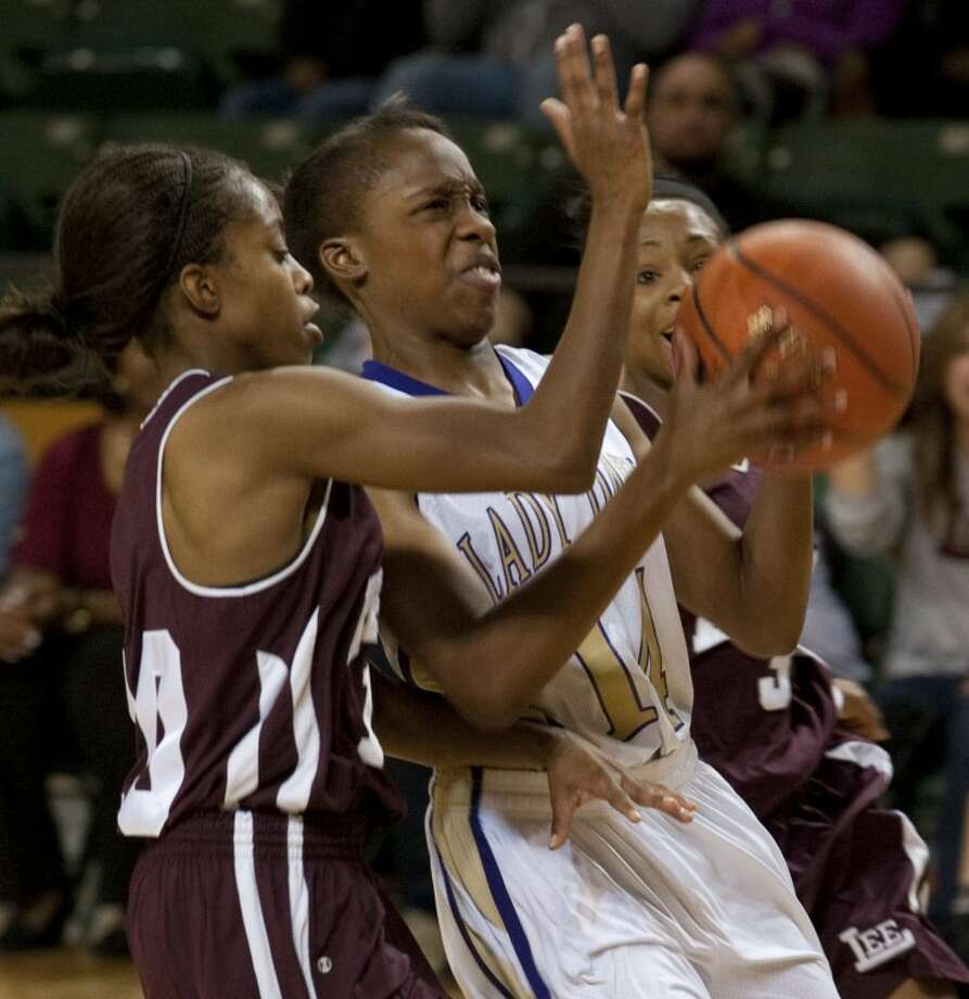 Midland High's Alexis Washington is fouled by Lee High's Daija Stanford as she drives the lane Thursday evening at the first round of the Byron Johnston Hoilday Classic at the Midland College Chaparral Center. Tim Fischer\Reporter-Telegram Photo: Tim Fischer