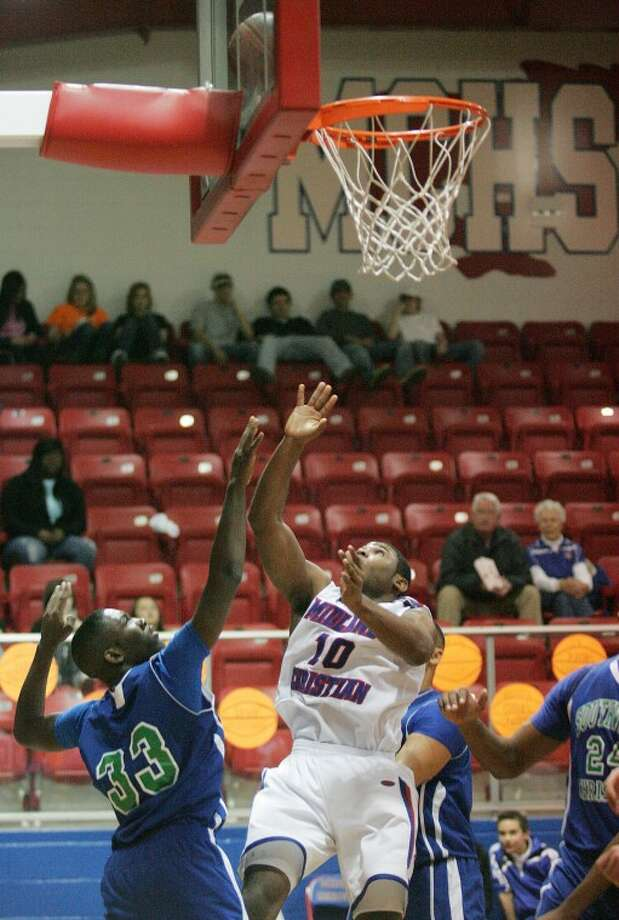 Devin Stricklin (10) takes the shot for two as he's guarded by Fort Worth Southwest Christian's Vince Evans (33), Saturday at McGraw Special Events Center, Midland Christian. Cindeka Nealy/Reporter-Telegram Photo: Cindeka Nealy