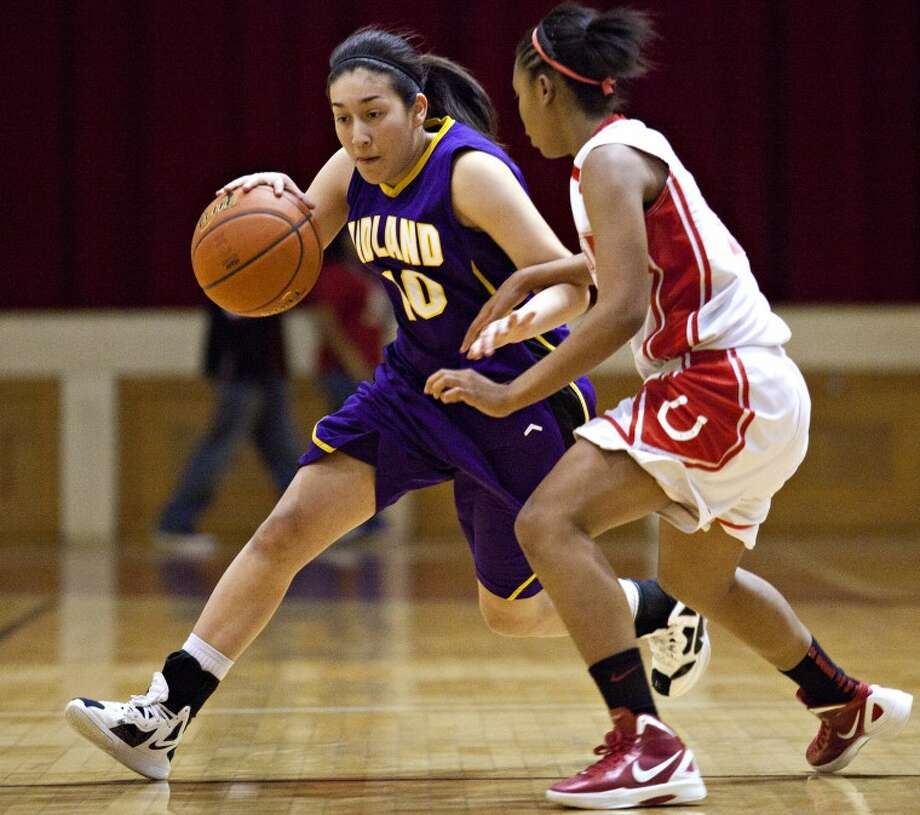 Midland High's Krystal Valdez (10) drives against Odessa High's Alex Carpio (5) during the game Tuesday at the Odessa High Field House. Photo: Courtesy Of Odessa American