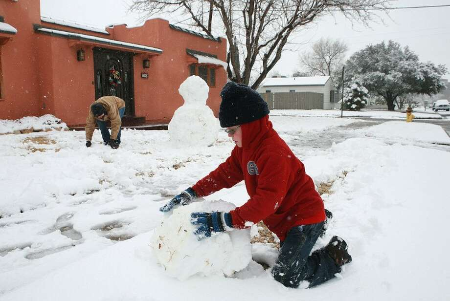 Leigh Ellis gathers snow while her son Jack, 9, rolls a snowball that will be the head of their snowman Monday on the 600 Block of Storey Avenue. Cindeka Nealy/Reporter-Telegram Photo: Cindeka Nealy