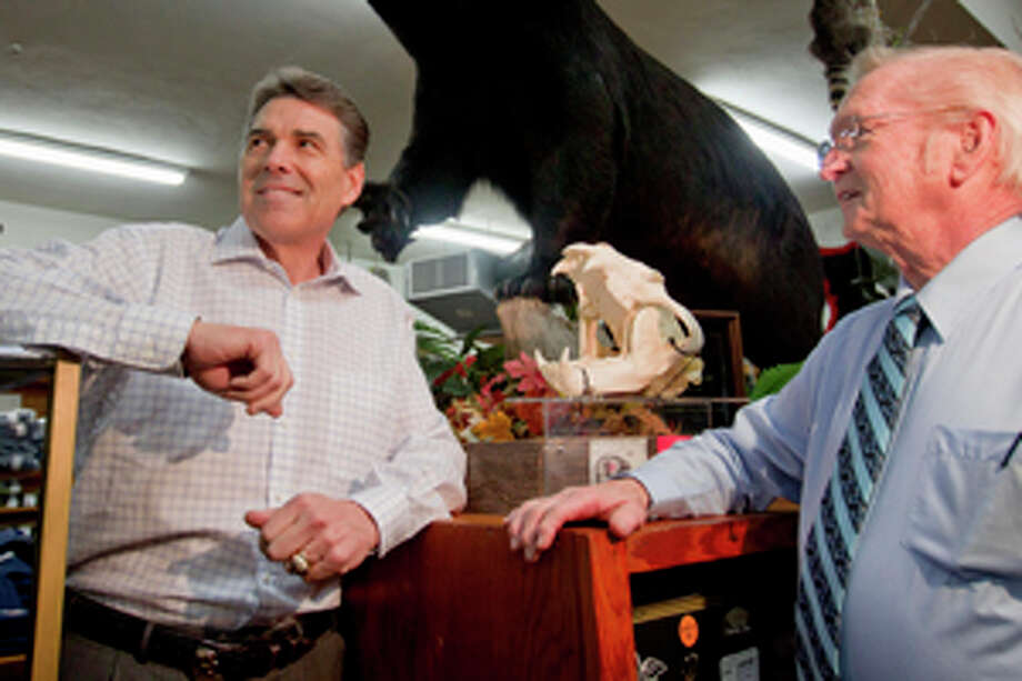 Republican presidential candidate, Texas Gov. Rick Perry stands under a black bear that was killed by the son of Glenn Brock, right, owner of Brock's department store during a campaign stop, Monday, Jan. 9, 2012, in Pickens, S.C. (AP Photo/David Goldman) Photo: David Goldman / AP