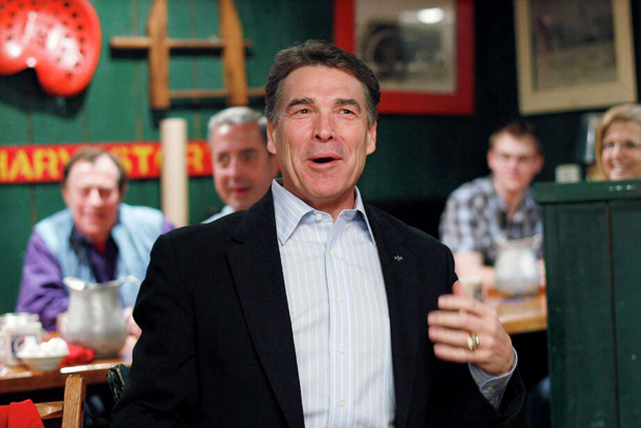 Republican presidential candidate, Texas Gov. Rick Perry laughs during a campaign stop at the Westside Conservative Club breakfast,Wednesday, Dec. 28, 2011, in Urbandale, Iowa. (AP Photo/Eric Gay) Photo: Eric Gay / AP