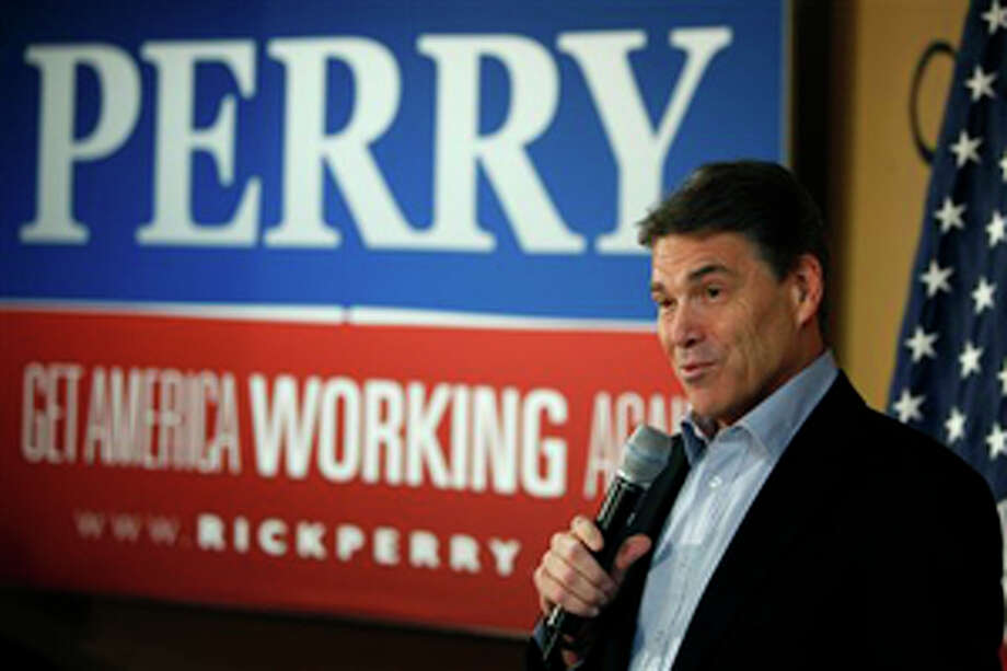 Republican presidential hopeful, Texas Gov. Rick Perry, speaks to local residents during a campaign stop at the Pizza Ranch restaurant, Monday, Dec. 19, 2011, in Manchester, Iowa. (AP Photo/Charlie Neibergall) Photo: Charlie Neibergall / AP