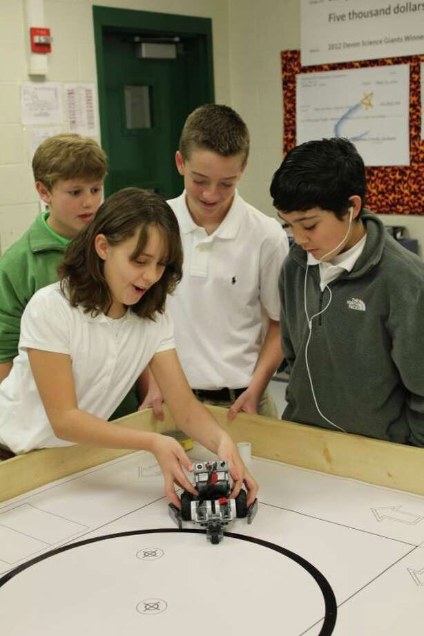 San Jacinto Jr. High robotics students Rian (yes, its correct spelling) Harper, Carter Petty, Cole Haskell and Hunter Ingram test out Team Spider's robot on the playing field Wednesday morning. This robot will compete against 31 others in the intermediate arena competition during Saturday's  Area 18 Robotics Competition, hosted at San Jacinto. Photo: Meredith Moriak/Reporter-Telegram
