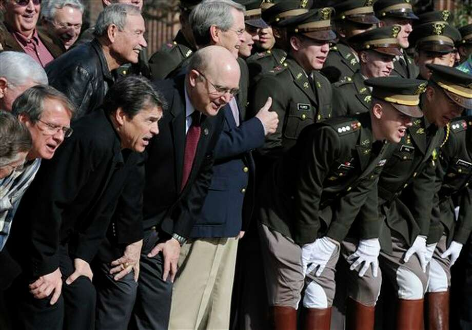 Texas Gov. Rick Perry, second from lower left, joins former and present members of the Texas A&M Corps of Cadets Squadron 6 following ceremonies marking the reactivation of the unit Friday, Jan. 11, 2013, in College Station, Texas. (AP Photo/Pat Sullivan) Photo: Pat Sullivan / AP