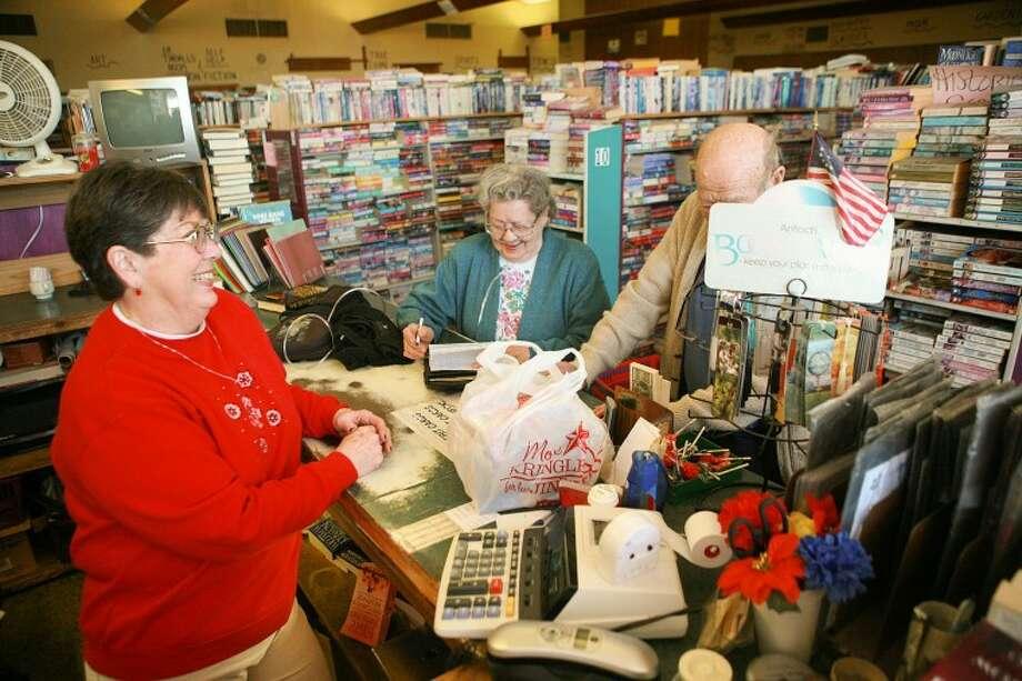 Sherry Dummer talks to longtime customers Genevieve and Carl Kaiser, Wednesday at Miz B's Used Book Store. Cindeka Nealy/Reporter-Telegram Photo: Cindeka Nealy