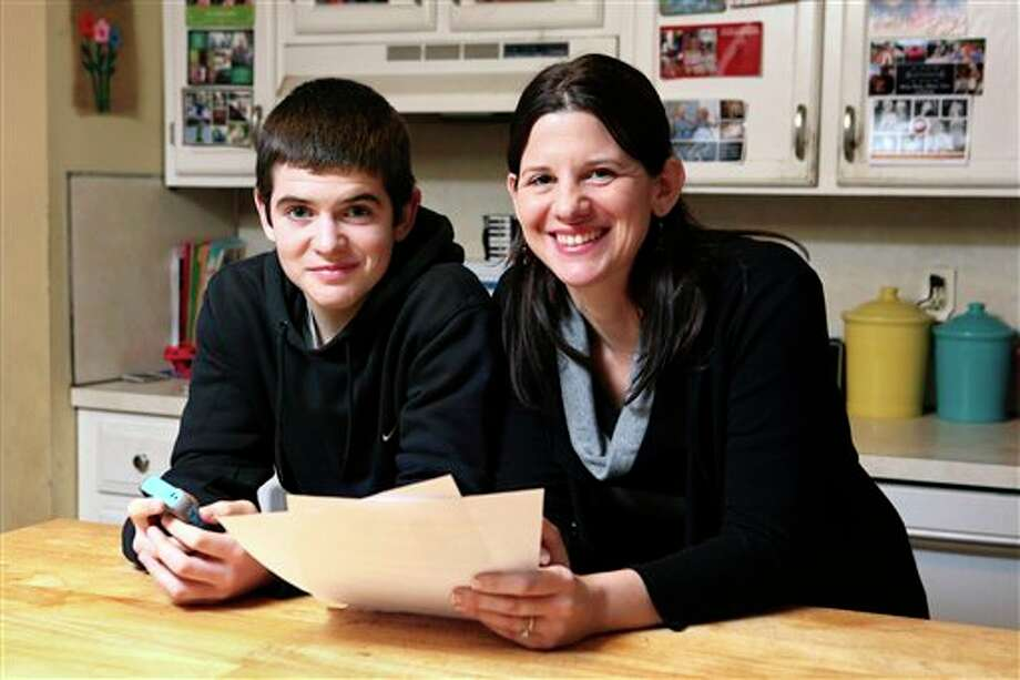 In this Jan. 4, 2013, photo, Janell Burley Hofmann, right, poses with her son Gregory at their home in Sandwich, Mass. Janell holds a copy of the contract she drafted and that Gregory signed as a condition for receiving his first Apple iPhone. (AP Photo/Michael Dwyer) Photo: Michael Dwyer / AP